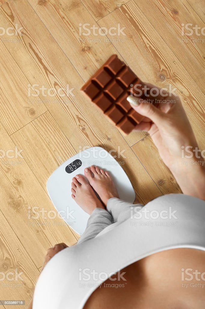 Diet. Woman On Weighing Scale, Chocolate. Unhealthy Food. Weight stock photo