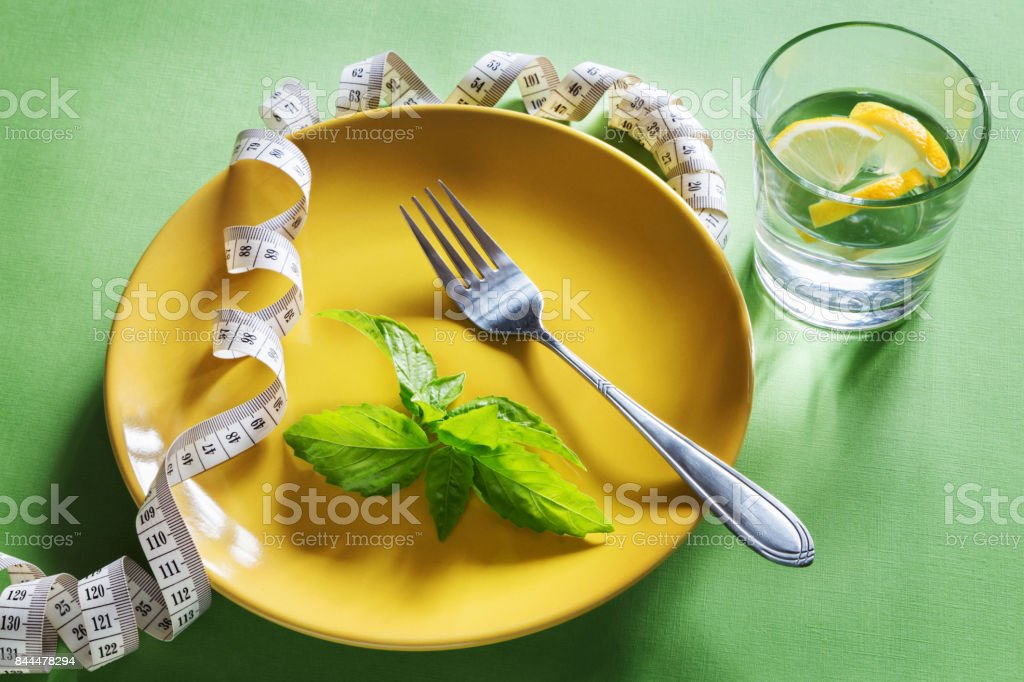 Diet yellow plate with centimeter, fork and basil stock photo