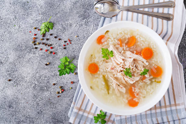 dietary chicken soup with rice and carrots. healthy food. flat lay. top view - chicken rice stock photos and pictures