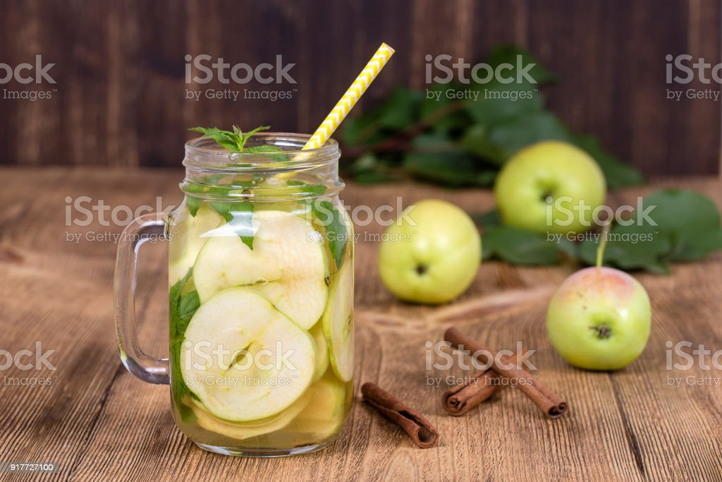Dietary detox drink with apple slices and mint leaves in clean water and a fresh apple on a wooden table, stock photo