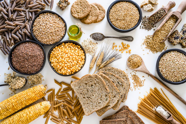 dietary fiber: large group of wholegrain food shot from above on white background - riso cereale foto e immagini stock