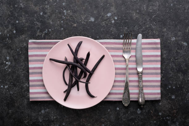 Dietary food purple asparagus bean pods on pink plate. Purple string asparagus bean pods on pink plate with cutlery on dark grunge table. Diet, Healthy eating concept. Top view. advisable stock pictures, royalty-free photos & images