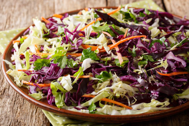 dietary home food: salad of white and red cabbage with carrots, herbs with olive oil close-up. horizontal - coleslaw stock pictures, royalty-free photos & images