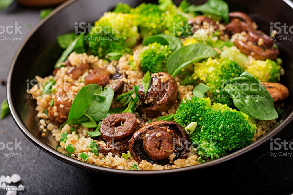 Dietary menu. Healthy vegan salad of vegetables - broccoli, mushrooms, spinach and quinoa in a bowl stock photo