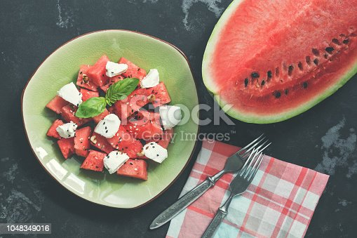 Dietary salad of watermelon and cheese on a stone rustic background. Top view.
