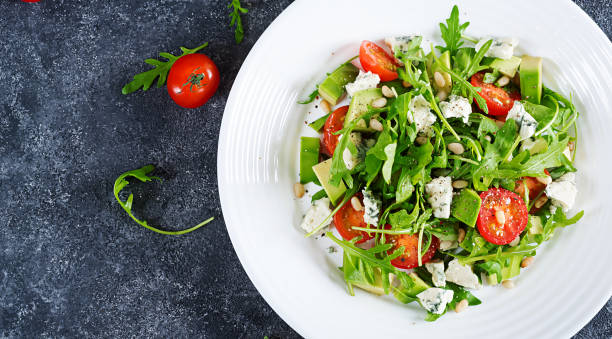 Dietary salad with tomatoes, blue cheese, avocado, arugula and pine nuts. Top view. Flat lay. stock photo