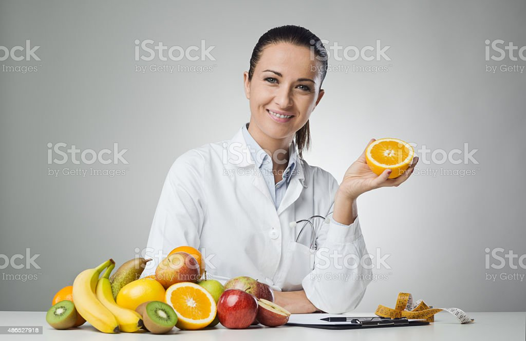 Dietician holding an orange stock photo