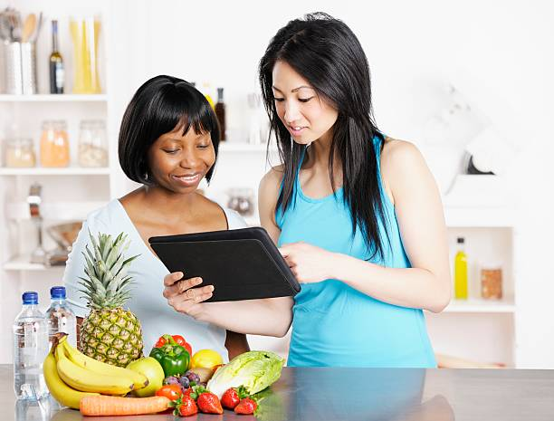 Dietician Showing Client Diet/ Food Plan On A Digital Tablet stock photo