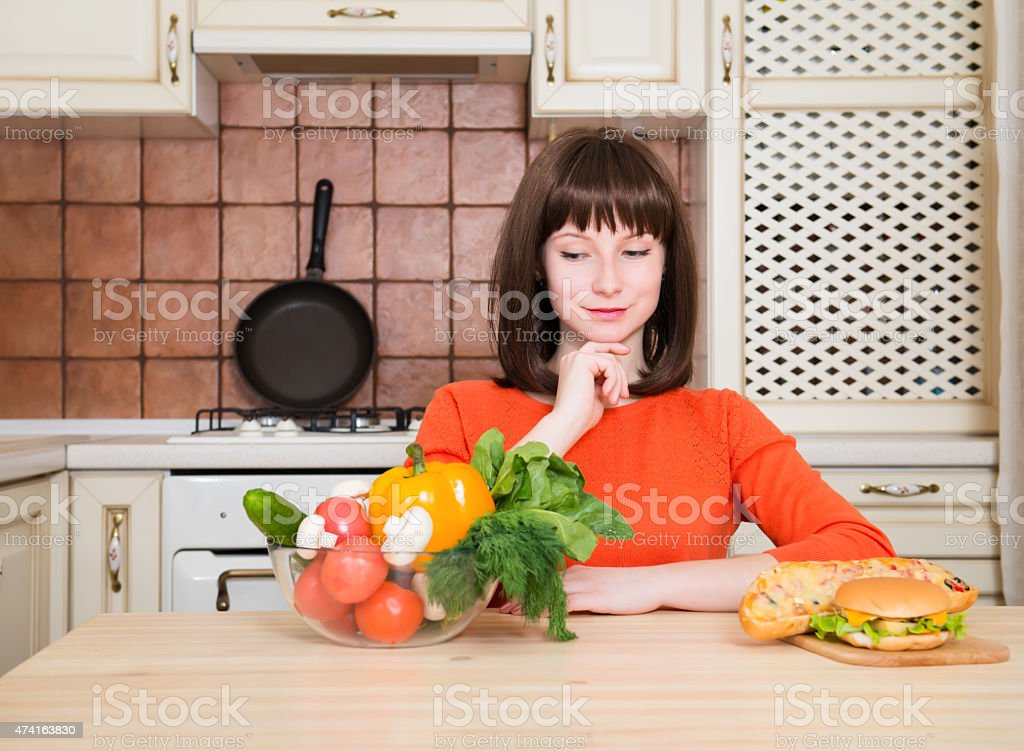 Dieting concept. Beautiful Woman Choosing Between Vegetables and Fast Food. stock photo
