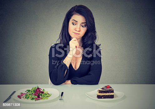 istock Dieting concept, beautiful young woman choosing between healthy food and tasty cake 839871308