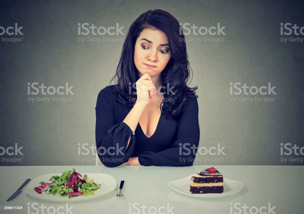 Dieting concept, beautiful young woman choosing between healthy food and tasty cake stock photo