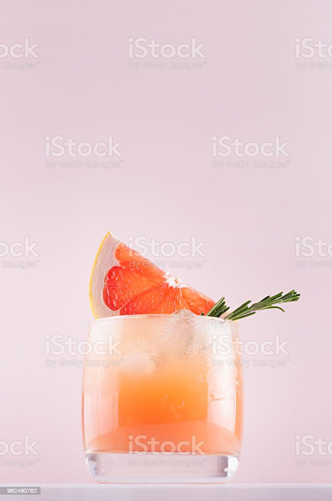 Dieting detox water with grapefruit juice, ice cubes, green rosemary, sliced citrus on soft pastel pink and white background. - Royalty-free Affectionate Stock Photo