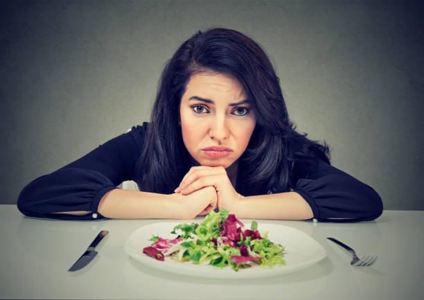 Dieting habits changes. Woman hates vegetarian diet stock photo
