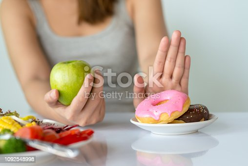 istock Dieting or good health concept. Young woman rejecting Junk food or unhealthy food such as donut or dessert and choosing healthy food such as fresh fruit or vegetable. 1092548998