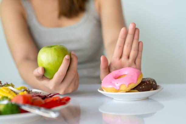 diyet ya da iyi sağlık kavramı. abur cubur veya çörek ya da tatlı gibi sağlıksız gıda reddetme ve taze meyve veya sebze gibi sağlıklı gıda seçimi genç kadın. - atıştırmalıklar stok fotoğraflar ve resimler