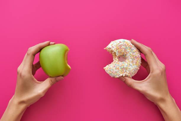 다이어트 또는 좋은 건강 개념. 애플과 도넛 사이 선택 하려고 하는 젊은 여자 - 악한 뉴스 사진 이미지