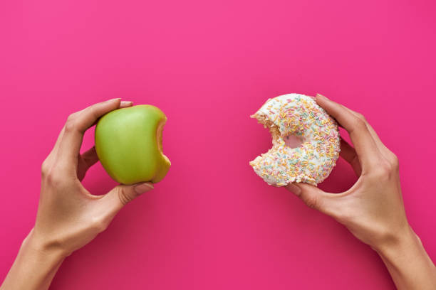 dieting or good health concept. young woman trying to choose between apple and donut - rudeness stock pictures, royalty-free photos & images