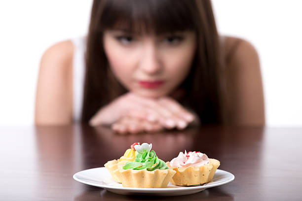 Dieting woman craving for cake Young dieting woman sitting in front of plate with delicious cream tart cakes, looking at forbidden food with unhappy and hungry expression, studio, white background, isolated, close-up temptation stock pictures, royalty-free photos & images