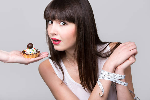 dieting woman got caught while trying to eat cake - funny fat lady stock photos and pictures