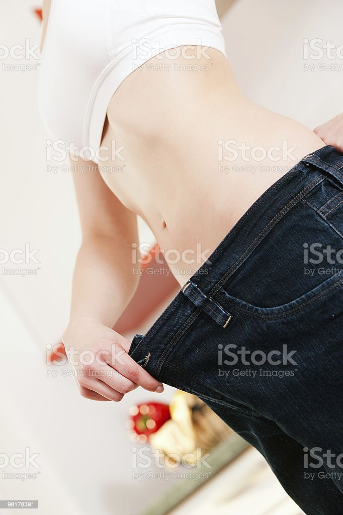 Dieting woman with oversized pants royalty-free stock photo