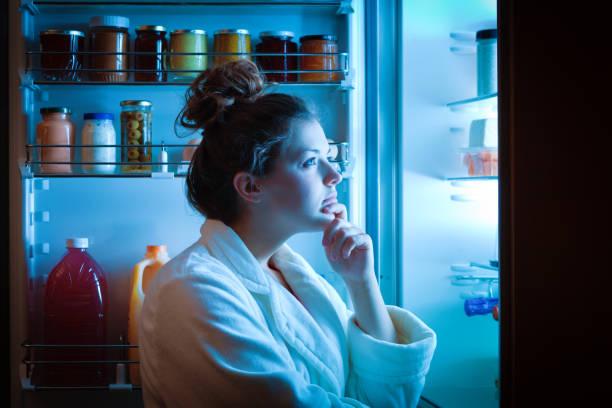 Dieta mujer joven tarde noche haciendo opciones sobre qué comer - foto de stock