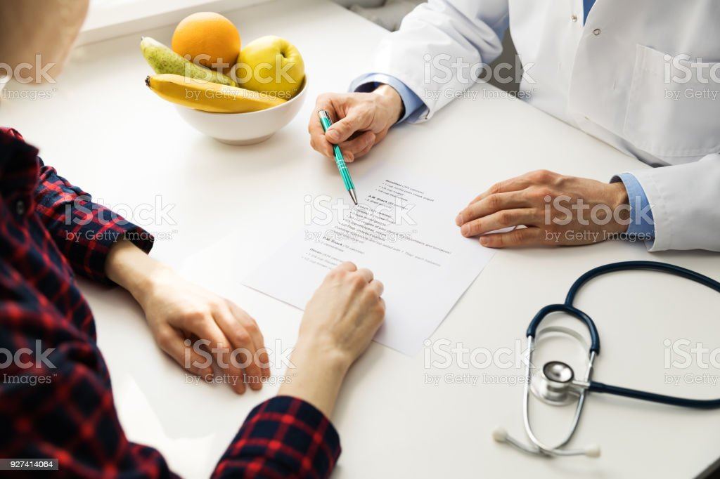 dietitian consultation - practitioner and patient discussing diet plan stock photo