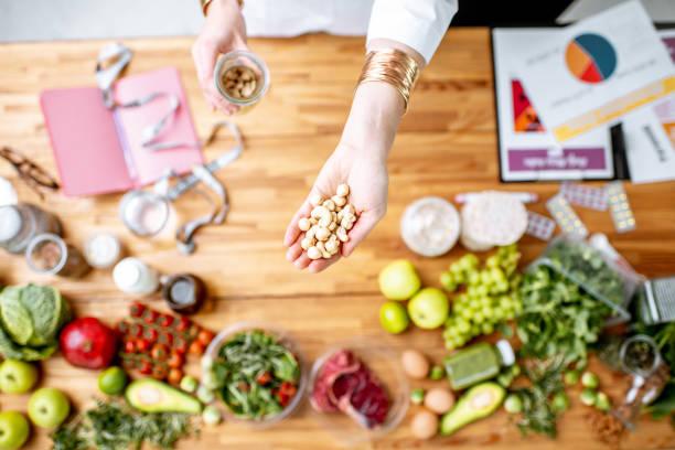 Ernährungsberater halten Nüsse über dem Tisch voll von gesunden Lebensmitteln – Foto