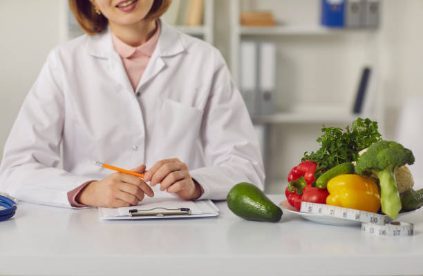 Dietitian sitting at table with fresh fruit, vegetables and individual diet plan stock photo