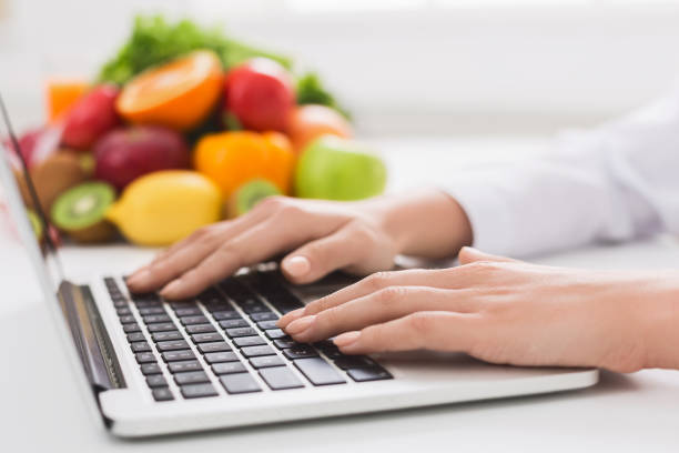 dietitian typing treatment to patient via internet - dietician stock pictures, royalty-free photos & images