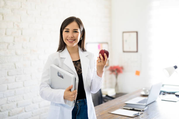Dietitian with weight scale and apple stock photo