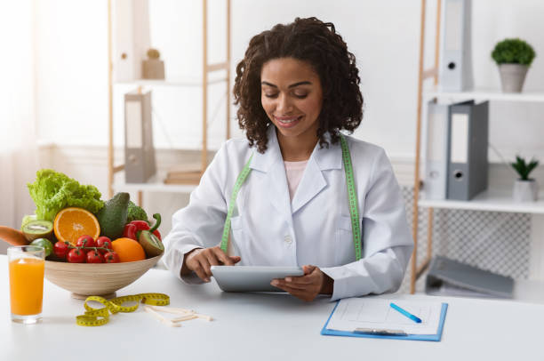 dietologist black woman working with digital tablet at workplace - dietician stock pictures, royalty-free photos & images