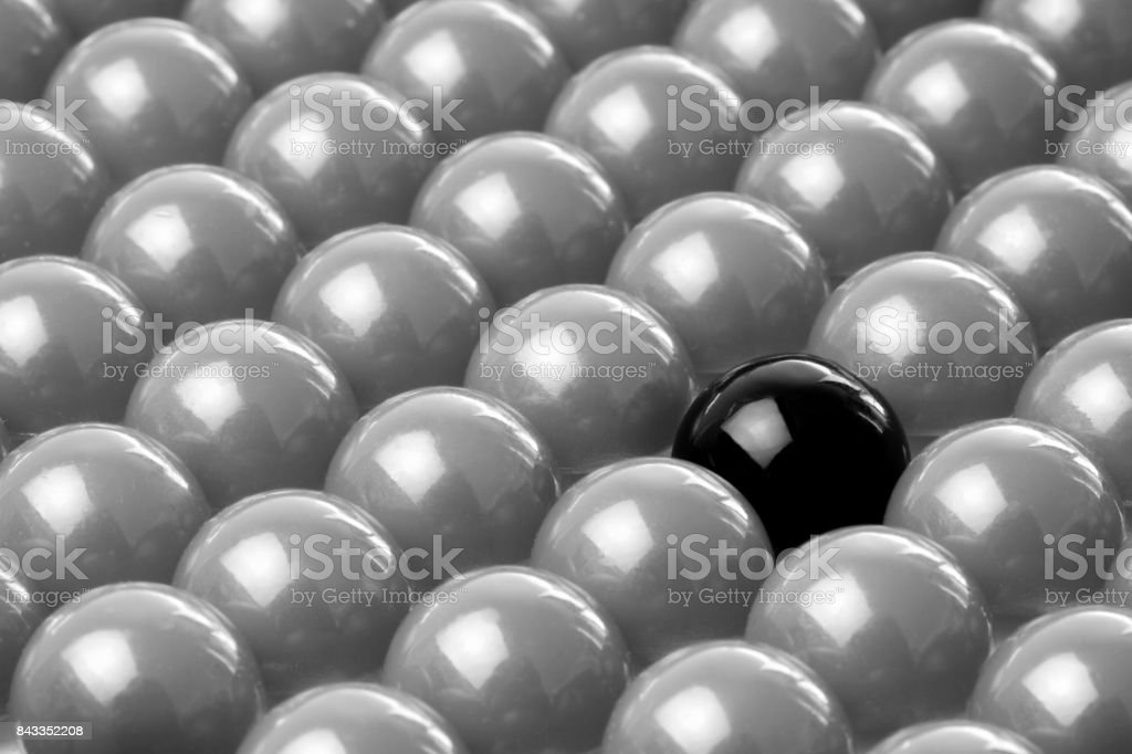Difference concept,  black ball in grey balls. stock photo
