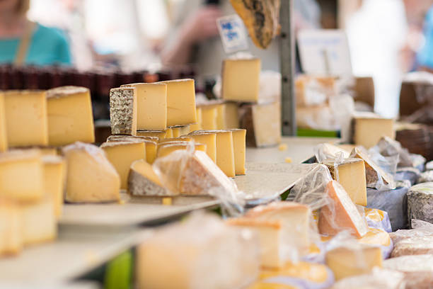 different aged cheese on a market stall - delis stock photos and pictures