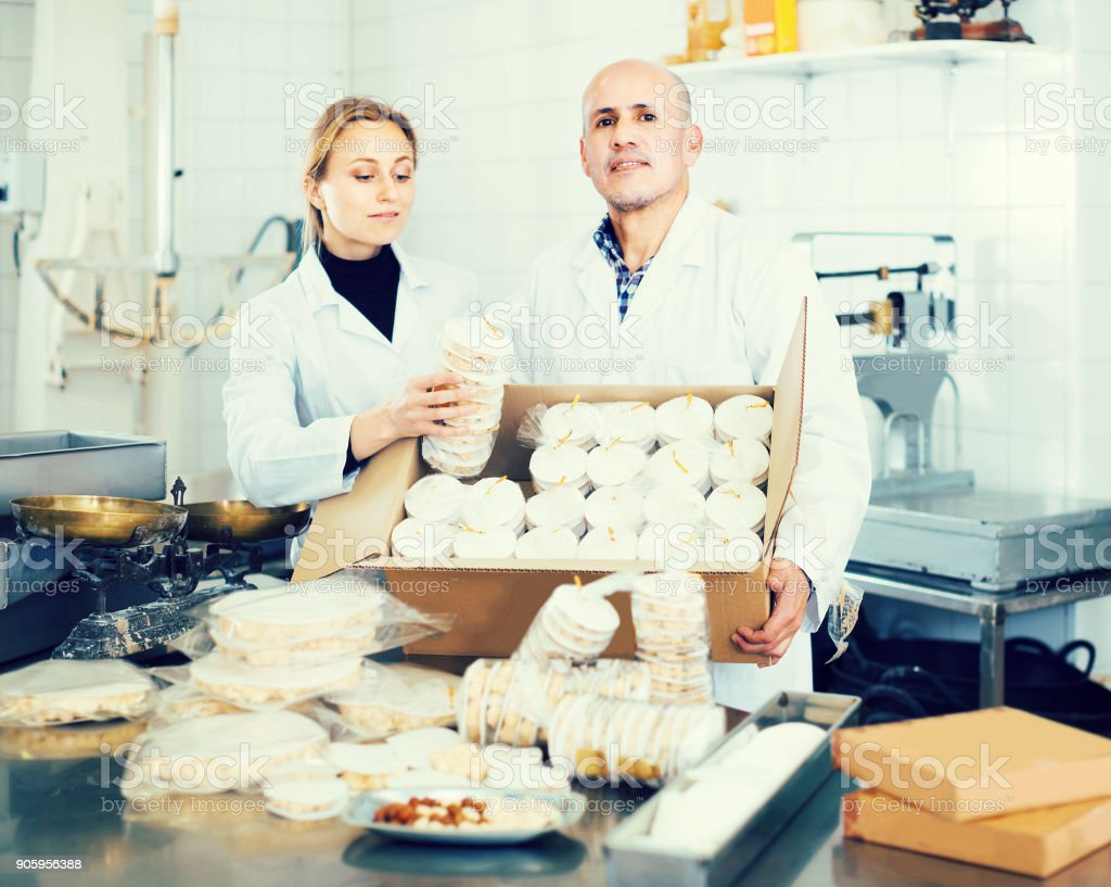 Different aged couple standing with box of turron in production workshop stock photo
