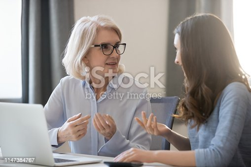 672116416istockphoto Different ages employees sitting at desk working together discussing project 1147384767