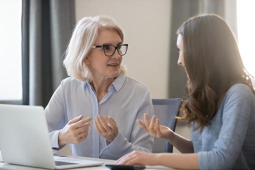 서로 다른 연령대의 직원이 함께 작업 하는 책상에 앉아 프로젝트를 논의 2명에 대한 스톡 사진 및 기타 이미지