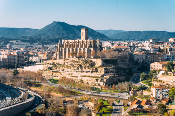 different and original view of Collegiate Basilica of Santa Maria Seu in Manresa city in catalunya region in Spain, with landscape of all the city stock photo