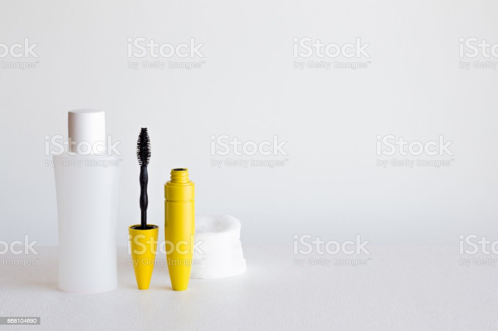 Different beauty products on the gray background. Black eyelashes...