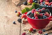 Ripe sweet different berries in red bowl on rustic wooden table. Harvest Concept