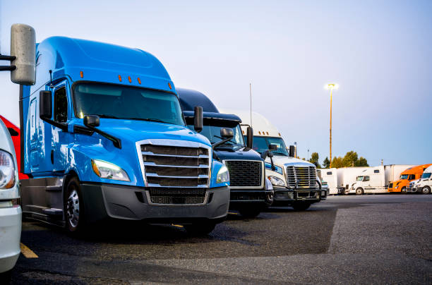 Different big rigs semi trucks standing in row on the truck stop parking lot at evening time stock photo