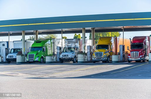 Different big rigs long and local haul semi trucks standing  under the eaves on the truck stop fuel station for refueling and continuation of the cargo delivery route according to the schedule