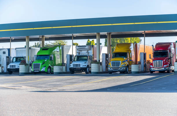 Different big rigs semi trucks standing on fuel station for truck refueling and continuation of the route stock photo