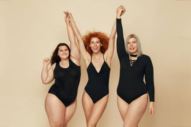 異なるボディタイプ。多様性モデルの肖像画のグループ。手をつないで黒いボディスーツを着た笑顔のブロンド、ブルネット、赤毛。幸せな生活のための女性の友情。 - real bodies ストックフォトと画像