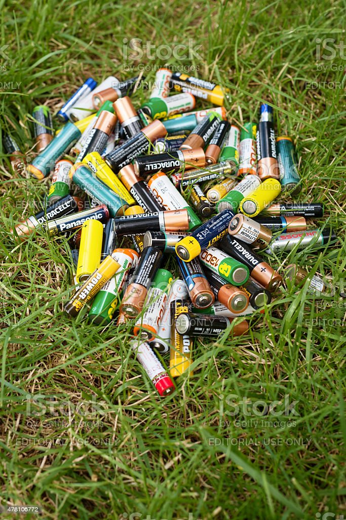 Different brand batteries on the grass stock photo