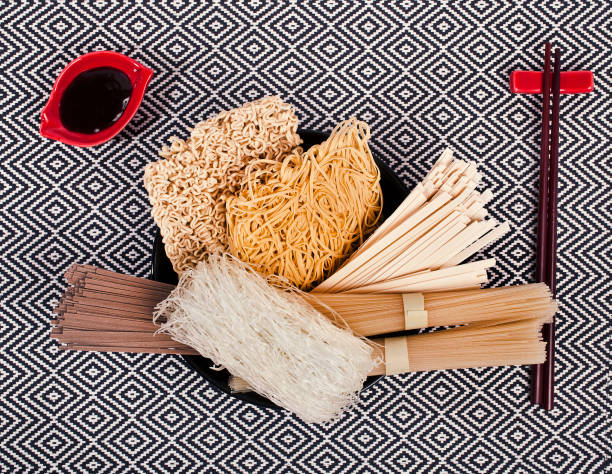 Different bundles of uncooked asian noodles. Different bundles of uncooked asian noodles (udon, soba, ramen, rice and glass noodles) in a black bowl with chopsticks and soy sauce on a patterned textile background. Top view. rice noodles stock pictures, royalty-free photos & images