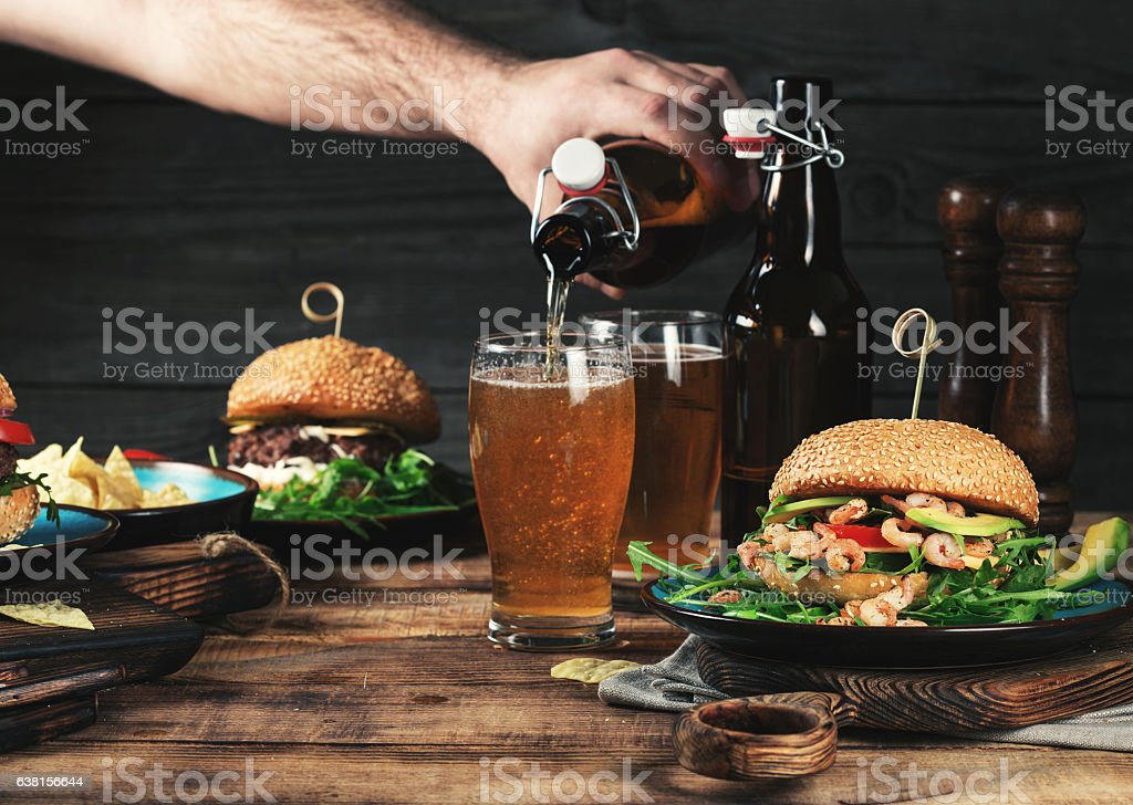 Different burgers with a light beer on a wooden table stock photo