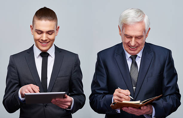 Different business habits Young businessman using digital tablet and senior businessman taking notes in personal organizer age contrast stock pictures, royalty-free photos & images