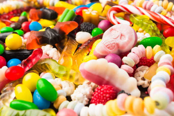 verschiedene süßigkeiten mit nahaufnahme rosa totenkopf für süsses oder saures - süßigkeit stock-fotos und bilder