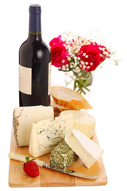 Different cheese with wine and roses stock photo