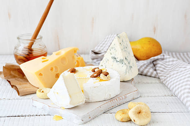 Different cheeses on a cutting board stock photo